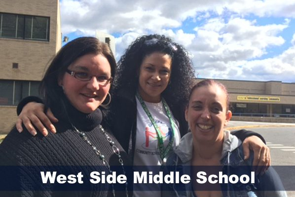 Staff posing in front of West Side Middle School